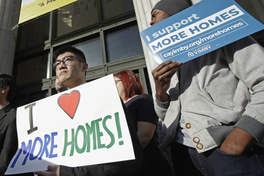 FILE - In this Jan. 7, 2020, file photo, men hold up signs at a rally outside of City Hall in Oakland, Calif. Californians are deciding whether to let cities expand rent control as the state's residents grapple with rising housing costs. Proposition 21 would let cities limit rent hikes on properties more than 15 years old. Individuals who own one or two single-family homes would be exempt. Proponents contend the measure is an urgent attempt to slow spiraling rent increases that lead to crowding and homelessness. Opponents argue the measure will discourage new home construction at a time when it is sorely needed for California's 40 million people.(AP Photo/Jeff Chiu, File)