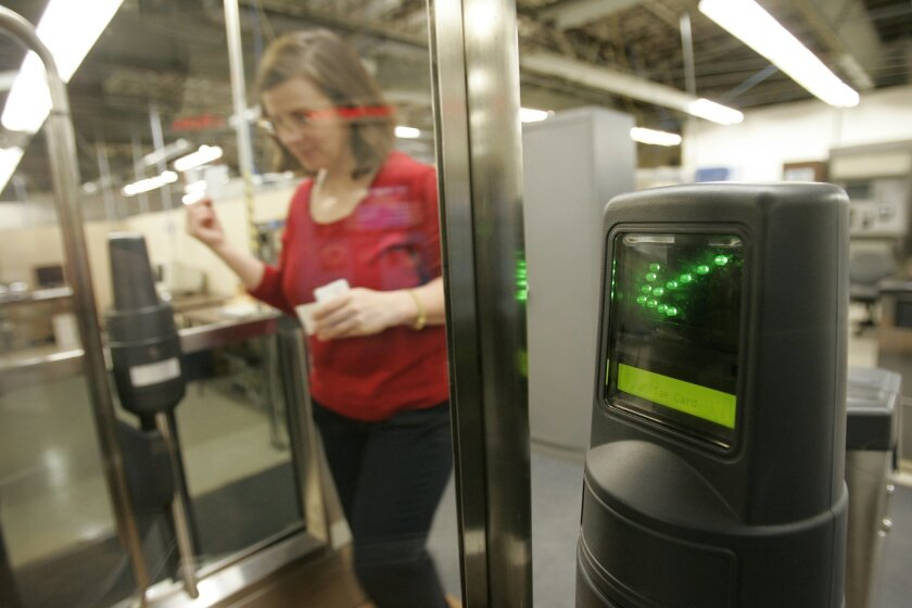 A Cubic Corp. employee tests one of the company's public transportation fare gates at Cubic headquarters in Kearny Mesa earlier this year.