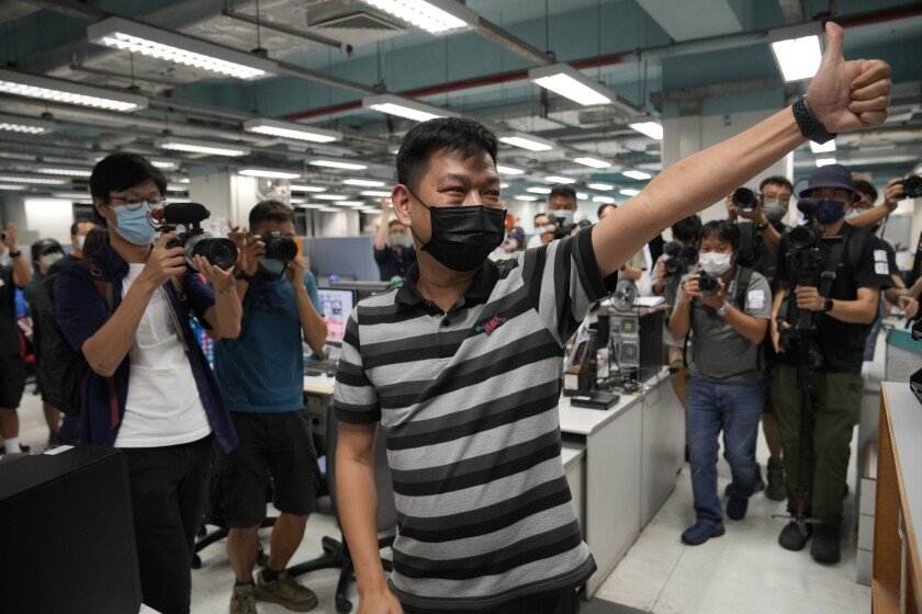 Lam Man-chung gives a thumbs-up in the Apple Daily newsroom as staffers take pictures and video.