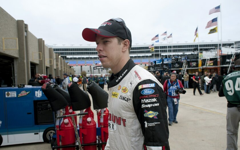 Brad Keselowski walks to the garage while waiting out a NASCAR auto race weather delay at Texas Motor Speedway Saturday, Nov. 7, 2015, in Fort Worth, Texas. (AP Photo/Ralph Lauer)