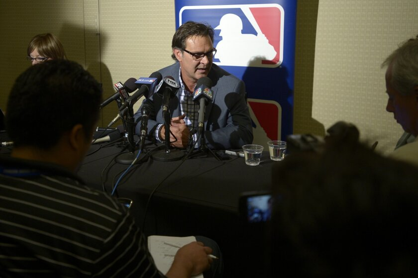 Los Angeles Dodgers manager Don Mattingly, center, takes a question from reporters during a media availability at baseball's winter meetings in Lake Buena Vista, Fla., Tuesday, Dec. 10, 2013.(AP Photo/Phelan M. Ebenhack)