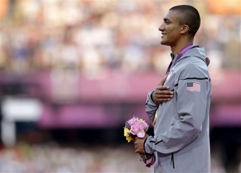 United States' Ashton Eaton listens to the U.S. national anthem after being presented with a gold medal in the men's decathlon during the athletics in the Olympic Stadium at the 2012 Summer Olympics, London, Friday, Aug. 10, 2012. (AP Photo/Matt Slocum)