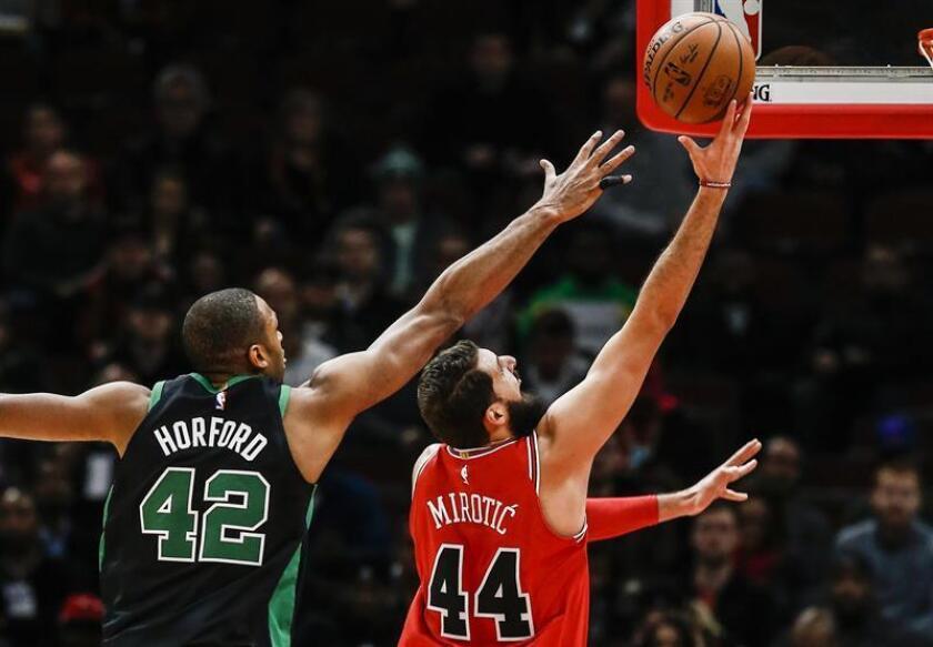 Nikola Mirotic (d), pívot montenegrino de los Bulls de Chicago, fue registrado este lunes al atacar el aro que defienden los Celtics de Boston, con la maraca de Al Horford (i), durante un partido de la NBA, en el United Center de Chicago (Illinois, EE.UU.). EFE