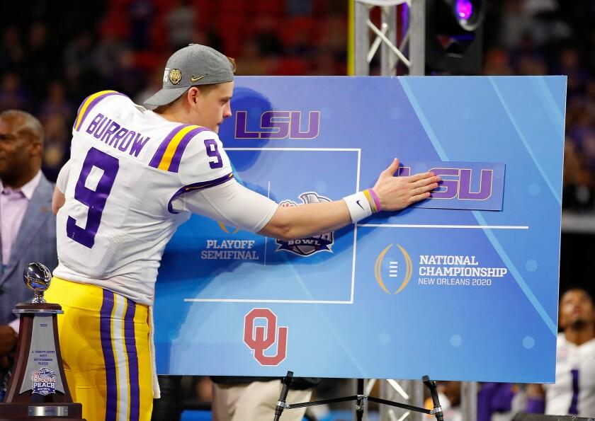 LSU quarterback Joe Burrow posts the LSU sticker on the bracket board to indicate advancing to the National Championship.