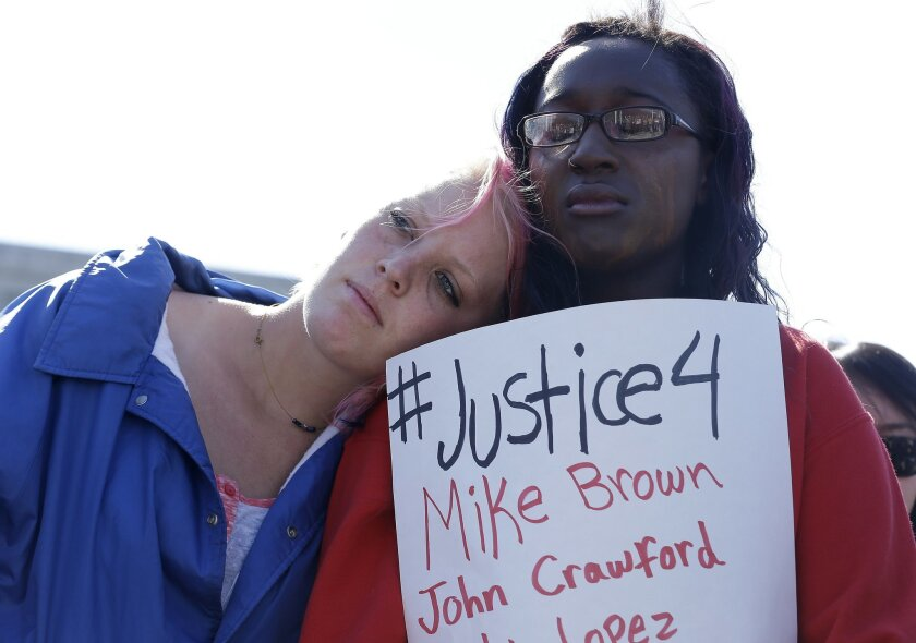 Savannah McCoy, 17, right, holds up a sign as she and her friend Kimber Camgros, 16, listen to speakers during a vigil for Michael Brown of Ferguson, Mo., in San Francisco, Thursday, Aug. 14, 2014. Brown, an unarmed black teenager, was killed by a white police officer on Saturday, Aug. 9, 2014. (AP