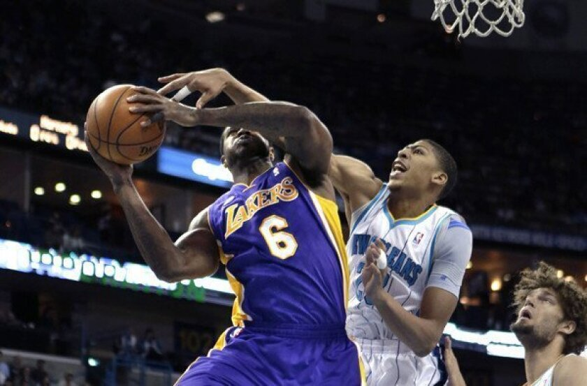 Hornets power forward Anthony Davis tries to block a shot by Lakers forward Earl Clark in the first half Wednesday night in New Orleans.