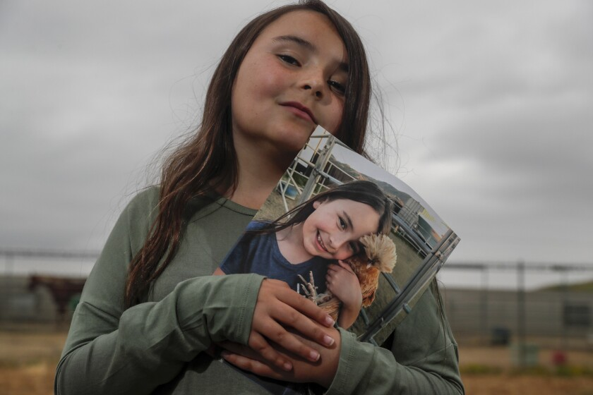 PERRIS, CA, THURSDAY, MAY 9, 2019 —Jada Hand, 9, holds a photo of her pet chicken, Bambi, who was re