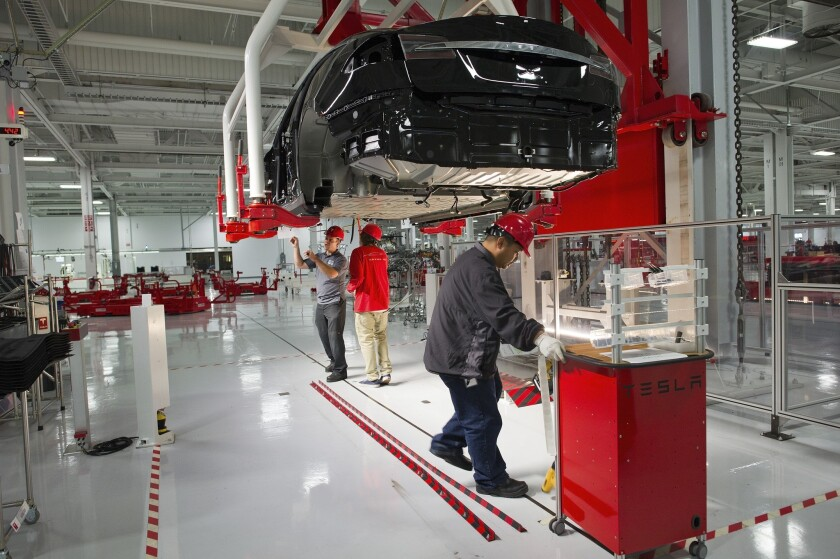 Tesla Motor Inc. associates work on the Model S electric car at the company's factory in Fremont, Calif.