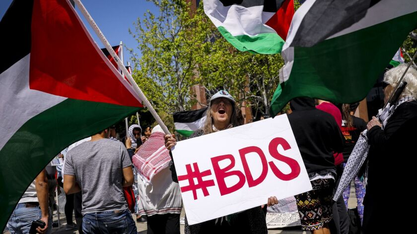 "A woman yells while holding a sign ""#BDS,"" referring to ""Boycott, Divestment, Sanctions,"" in front of the Israeli Consulate in Los Angeles on May 14."