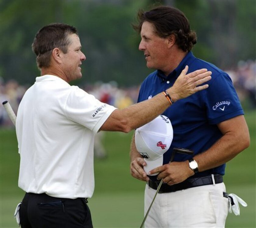 Scott Verplank, left, congratulates Phil Mickelson, right, on winning the Houston Open PGA Tour golf tournament on Sunday, April 3, 2011, in Humble, Texas. Mickelson won the tournament with a 20-under par 268. (AP Photo/Dave Einsel)