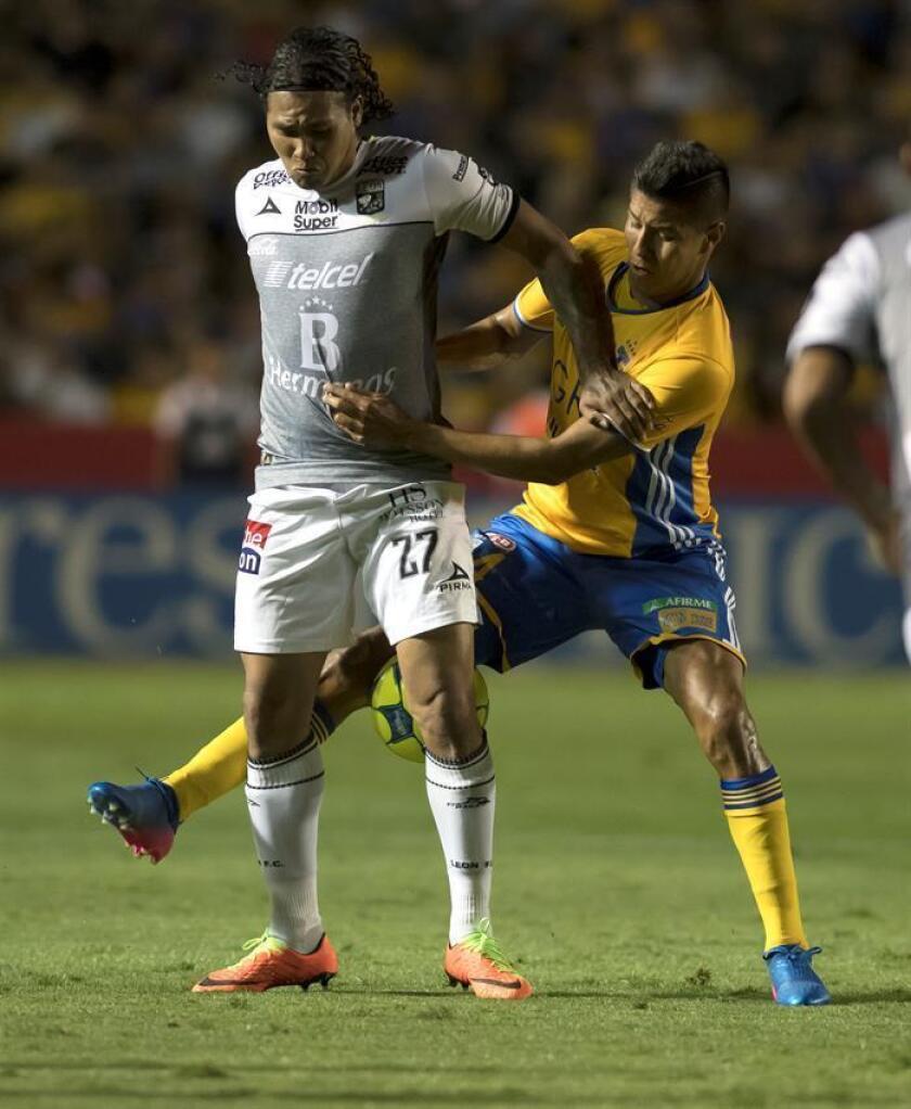 Hugo Ayala (d) de Tigres disputa el balón con Carlos Peña (i). EFE/Archivo