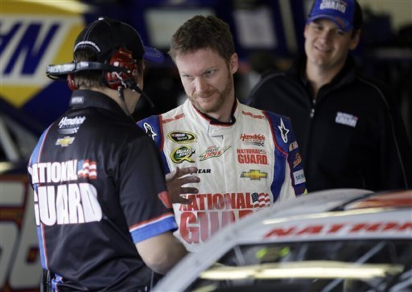 Dale Earnhardt Jr., center, talks with a crew member in his garage as crew chief Steve Letarte, right, listens during practice for the NASCAR Daytona 500 Sprint Cup Series auto race at Daytona International Speedway, Saturday, Feb. 16, 2013, in Daytona Beach, Fla. (AP Photo/John Raoux)