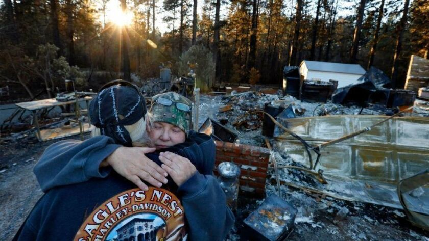 Kathy Tyler gets a hug from friend Russ Vaugh after they work to recover what was left of the Tyler home following the Camp fire in Northern California. Kathy and her husband, Charles Tyler, had lived in the area since 2002.