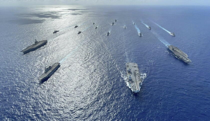 In this photo released by the U.S. Indo-Pacific Command, the United Kingdom's carrier strike group led by HMS Queen Elizabeth (R 08), and Japan Maritime Self-Defense Forces led by (JMSDF) Hyuga-class helicopter destroyer JS Ise (DDH 182) joined with U.S. Navy carrier strike groups led by flagships USS Ronald Reagan (CVN 76) and USS Carl Vinson (CVN 70) sails to conduct multiple carrier strike group operations in the Philippine Sea, Oct. 3, 2021. A spate of recent Chinese military flights off Taiwan, which Beijing claims as its own, and naval maneuvers by the United States and its allies to reinforce maritime routes challenged by China are fueling increasing tensions in a region already on edge. (Gray Gibson/U.S. Navy via AP)