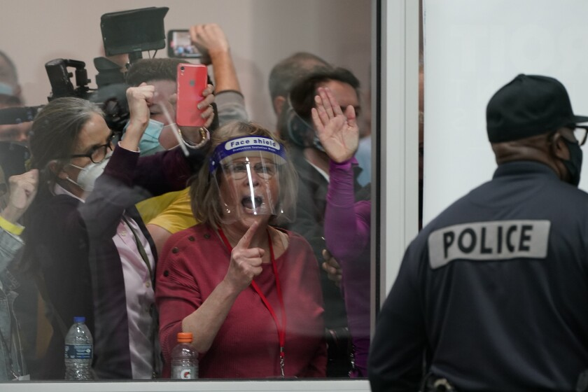 """A man in a jacket labeled """"Police"""" stands near a window, behind which people yell and press their hands to the glass."""
