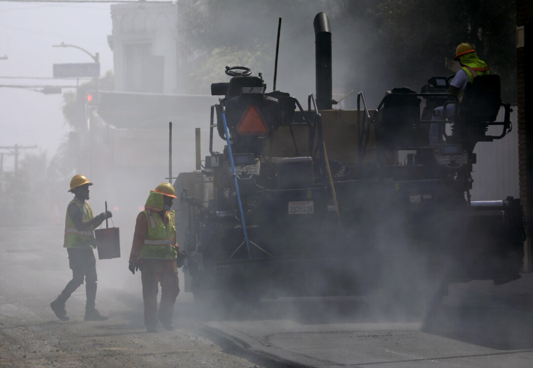 Construction workers lay asphalt