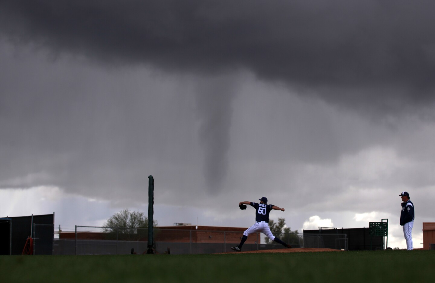 San Diego Padres pitcher Brett Kennedy throws as a funnel cloud appears off in the distance during a spring training practice on Feb. 22, 2019.