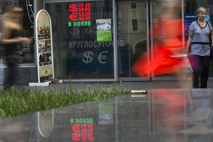 People walk past an exchange office sign showing the currency exchange rate in Moscow, Russia, Monday, July 27, 2015. The Russian ruble dropped by 2 percent on Monday, to nearly 60 rubles against the dollar, battered by low oil prices.(AP Photo/Alexander Zemlianichenko)