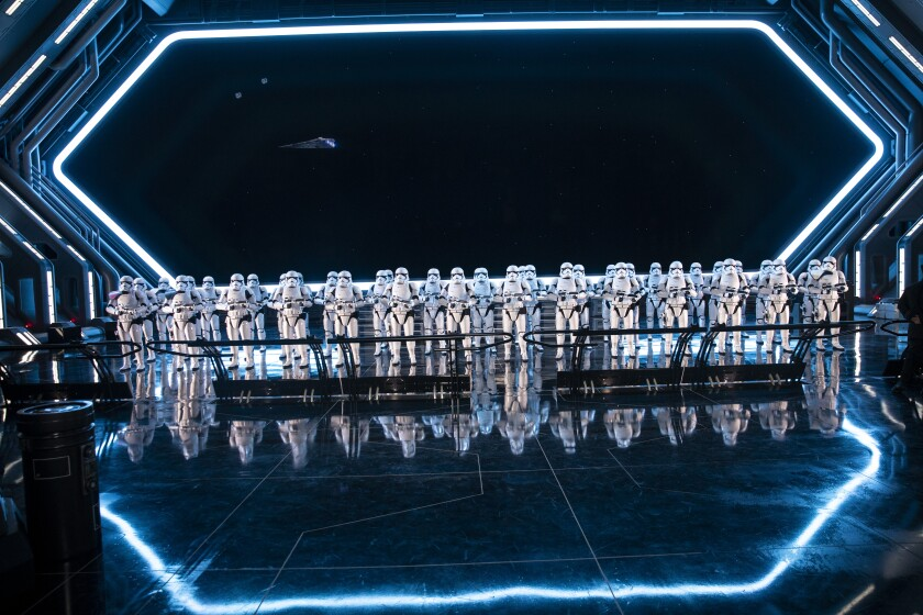 A crowd of Stormtroopers standing in front of a giant window looking out into space