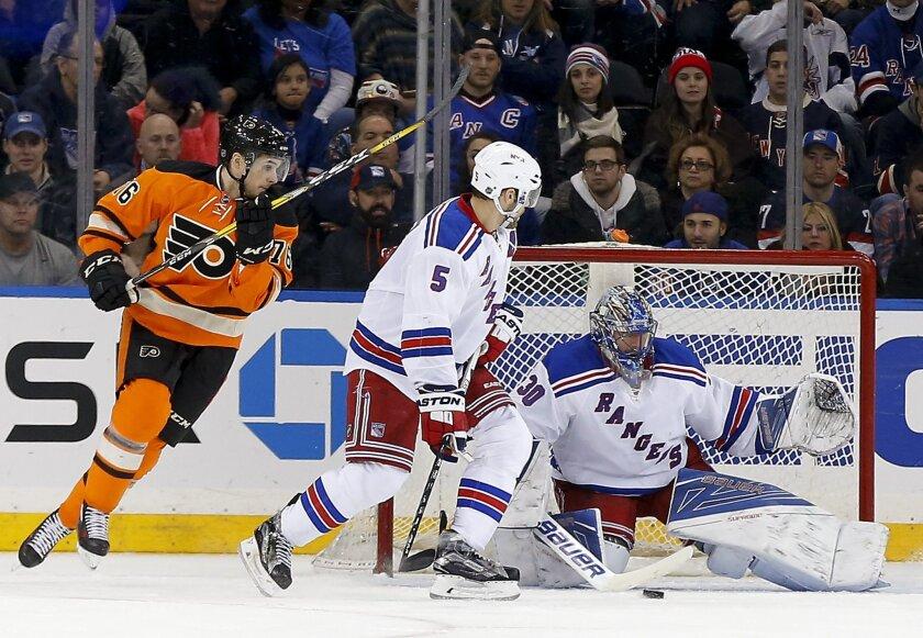 Philadelphia Flyers center Chris VandeVelde (76) and New York Rangers defenseman Dan Girardi (5) look for the rebound as goalie Henrik Lundqvist (30) blocks a shot during the second period of an NHL hockey game, Sunday, Feb. 14, 2016, in New York. (AP Photo/Julie Jacobson)
