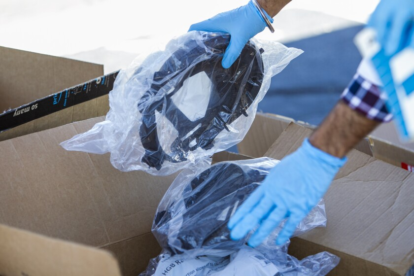 Jaspal Bassi, a first-year UC Irvine medical student, organizes face shields Monday during a drive to collect donated personal protective equipment for medical workers.
