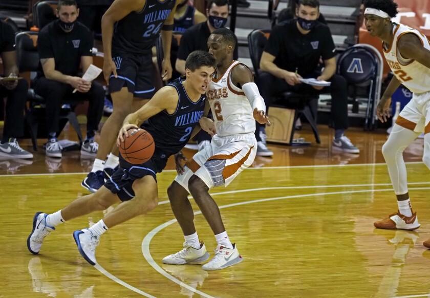 Villanova guard Collin Gillespie, left, drives the ball around Texas guard Matt Coleman, III, right, during the second half of an NCAA college basketball game, Sunday, Dec. 6, 2020, in Austin, Texas. Villanova won 68-64. (AP Photo/Michael Thomas)