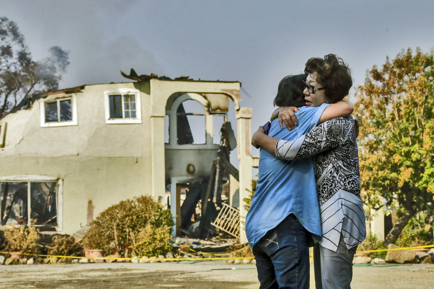 Aurora Harris Heller, 62, left, comforts the owner of a home destroyed in the Sand fire in Santa Clarita.