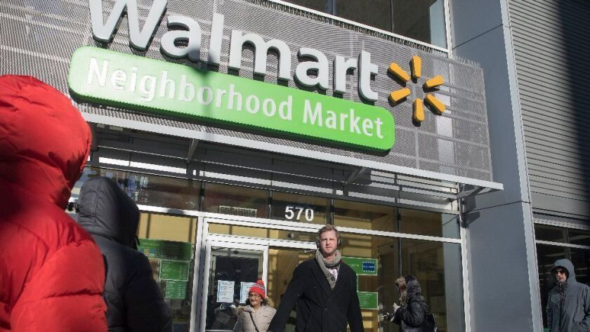 Customers exit and enter the Walmart at Presidential Towers on Jan. 4, 2017, in West Loop Gate. The retailer lowered its earnings predictions for fiscal 2019, citing the impact of its $16 billion acquisition of Flipkart, an Indian online retailer.