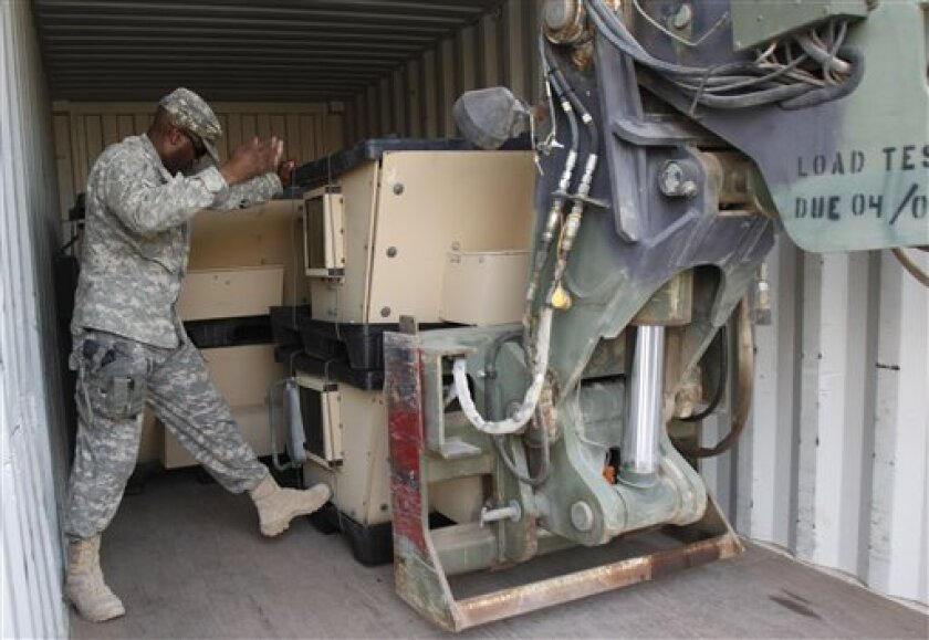 A U.S Army Soldier loads military equipments after a hand-over ceremony of a military base in Basra, 340 miles (550 kilometers) southeast of Baghdad, Iraq, Wednesday, Sept. 7, 2011. James F. Jeffrey on Wednesday dismissed a proposal to keep as few as 3,000 troops as not credible, signaling a debate between President Obama's advisers in Baghdad and Washington of the U.S. military's future in Iraq with time running out to decide. (AP Photo / Nabil al-Jurani)