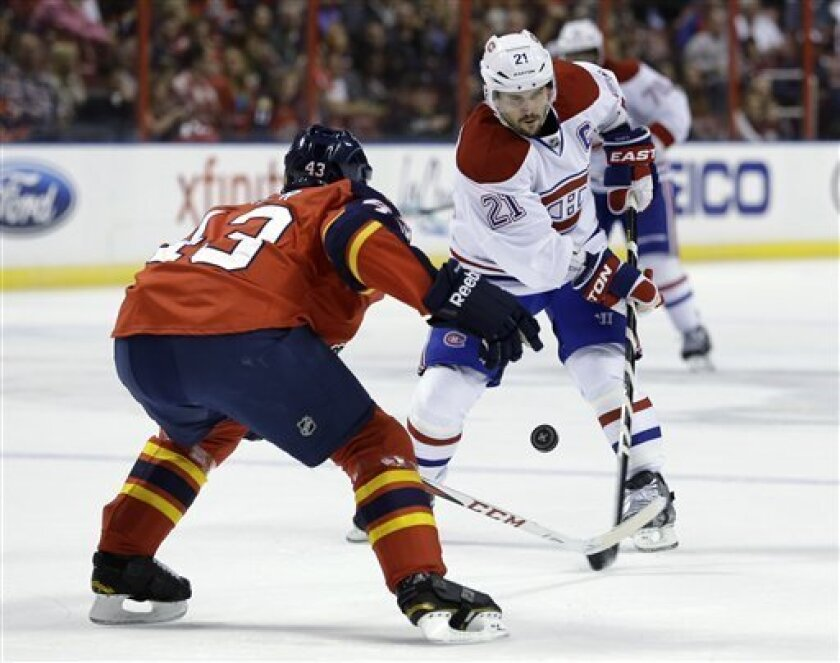 Montreal Canadiens right wing Brian Gionta (21) passes the puck past Florida Panthers defenseman Mike Weaver (43) during the first period of an NHL hockey game, Thursday, Feb. 14, 2013, in Sunrise, Fla. (AP Photo/Wilfredo Lee)
