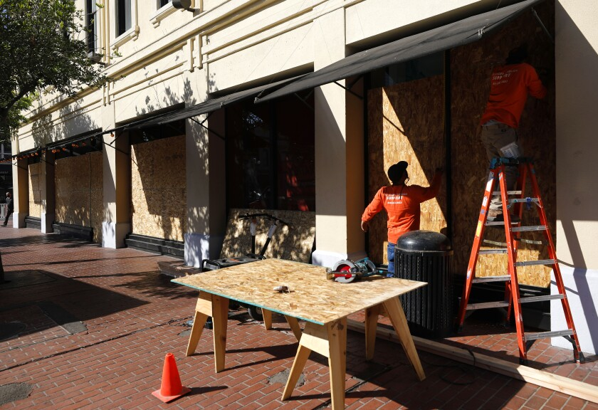Workers board up the windows at Searsucker restaurant in the the Gaslamp Quarter on Monday, Nov. 2, 2020 in San Diego, CA.