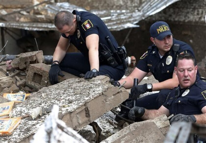 Moore police dig through the rubble of the Plaza Towers Elementary School following a tornado in Moore, Okla., Monday, May 20, 2013. A tornado as much as a mile (1.6 kilometers) wide with winds up to 200 mph (320 kph) roared through the Oklahoma City suburbs Monday, flattening entire neighborhoods,