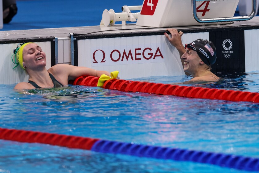 Australia's Ariarne Titmus, left, smiles after beating U.S. swimmer Katie Ledecky, right, for the gold medal.
