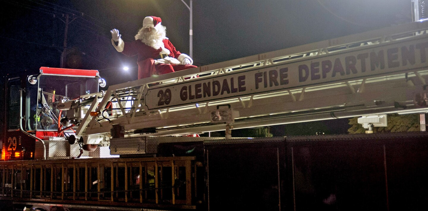 Riding on the back of A Glendale Fire Department ladder truck, Santa waves to the crowd along Honolulu Avenue during the annual Montrose Glendale Christmas Parade Saturday.