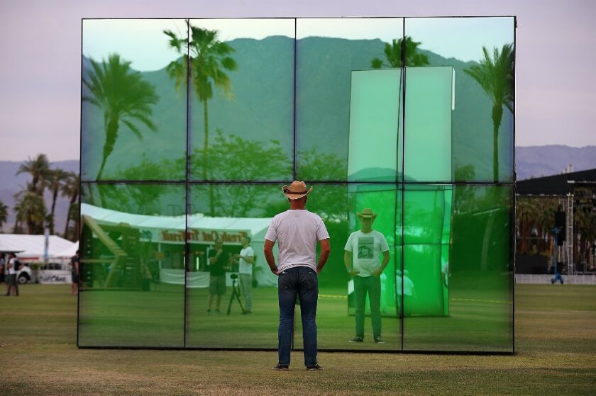 """A festival-goer gazes into the art installation """"Reflection Field,"""" by Phillip K. Smith, at the Coachella Music and Arts Festival in Indio, Calif."""