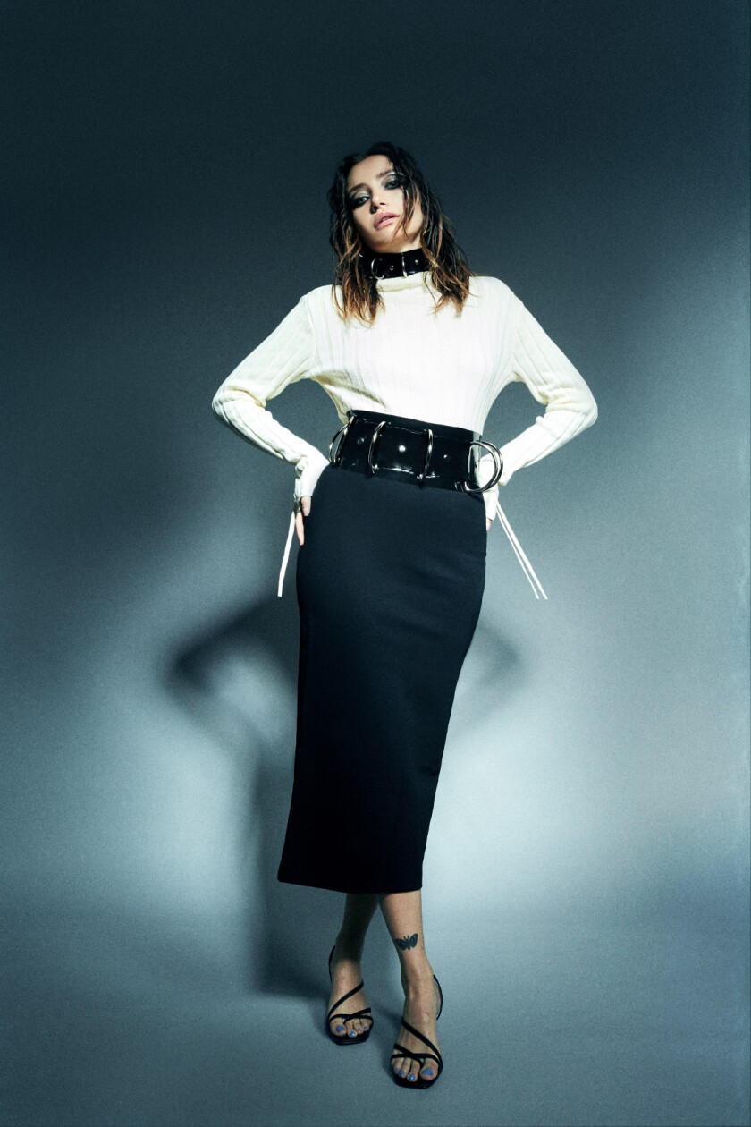 A model wears a black pencil skirt with a white long-sleeved top and a wide black belt and choker.
