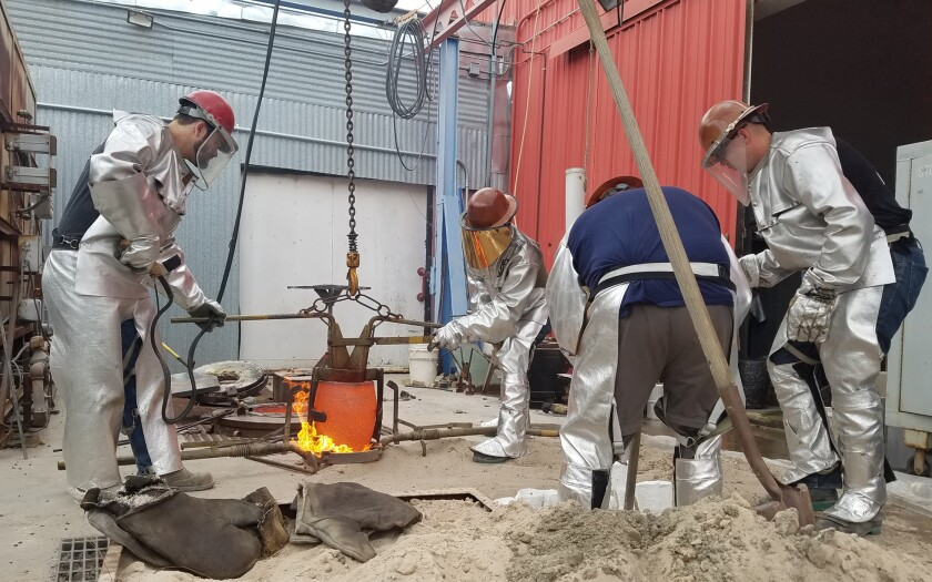 Military veterans work with molten bronze at the Veterans Art Project's foundry in Fallbrook in this undated photo.