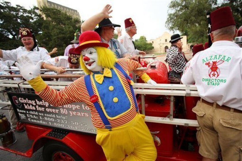 """""""Howie-U"""" the clown, middle, and fellow Shriners wave to spectators from an antique fire truck during the Shriners' Imperial Parade, Tuesday, July 7, 2009, in San Antonio. (AP Photo/Darren Abate)"""