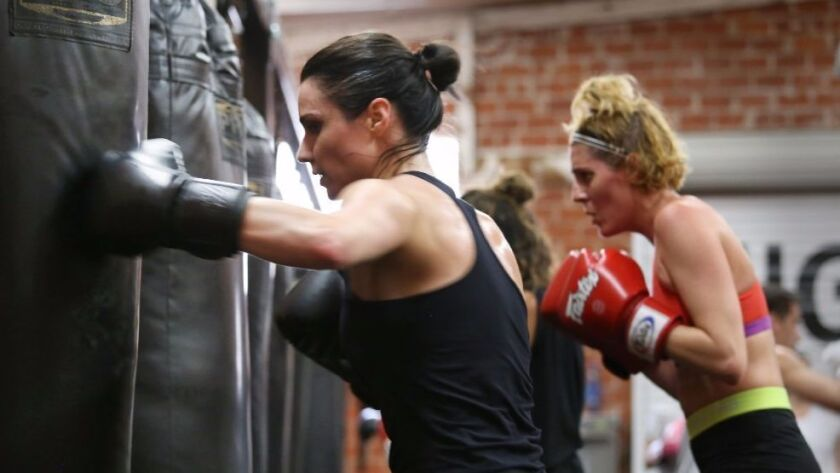 Jensen Jacobs, left, and J.C. Coccoli hit the heavy bag during the boxing fitness class at Prevail B