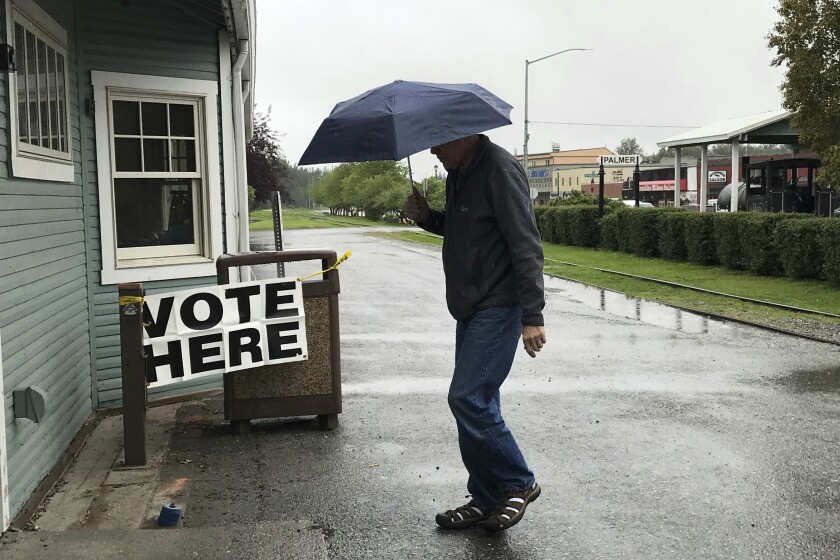 """FILE - In this Aug. 21, 2018 file photo, a voter enters the Palmer Community Center to cast their ballot in Alaska's primary election, on a rainy in Palmer, Alaska. The Alaska Republican Party has canceled holding a presidential primary in 2020. In a statement Saturday, Sept. 21, 2019, the party's State Central Committee passed a rule saying a primary """"would serve no useful purpose"""" because Republican Donald Trump is president. (Bill Roth /Anchorage Daily News via AP, File)"""