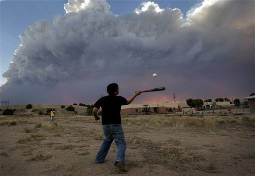 Alex Lopez, center, plays baseball with his sister Sugey while smoke generated by the Las Conchas fire covers the sky in Espanola, N.M., Wednesday, June 29, 2011. As crews fight to keep the wildfire from reaching the country's premier nuclear-weapons laboratory and the surrounding community, scient