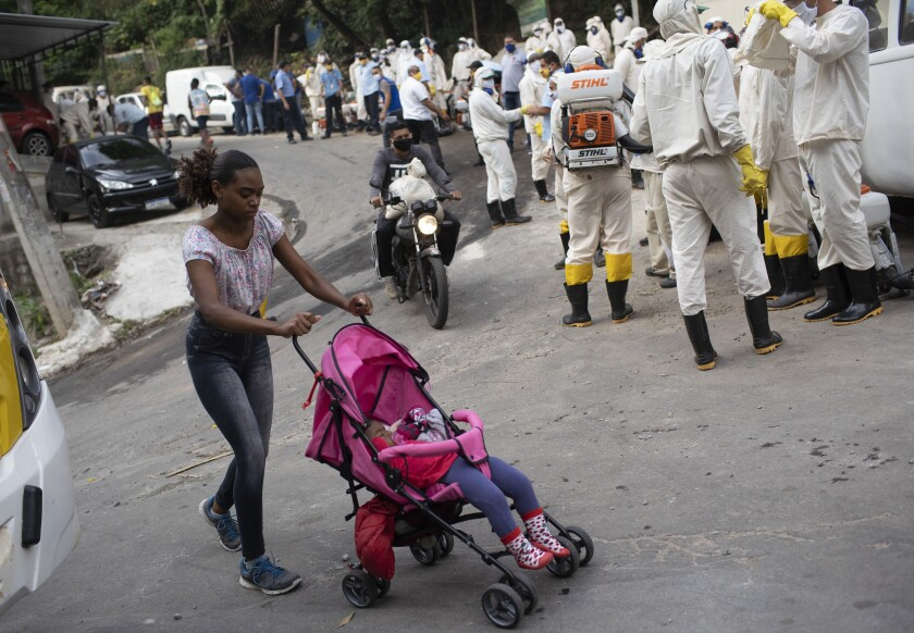 A woman walks past workers who will disinfect the Turano favela in an effort to curb COVID-19's spread  in Rio de Janeiro.