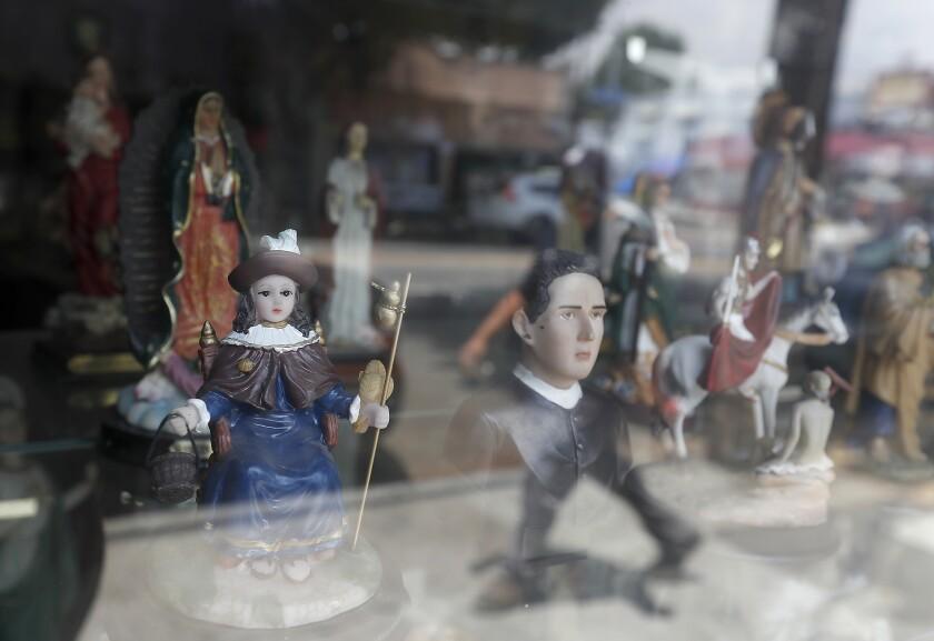 A figurine of Santo Niño de Atocha, left, shown in a display window of a botánica on Cesar Chavez Boulevard in Boyle Heights.