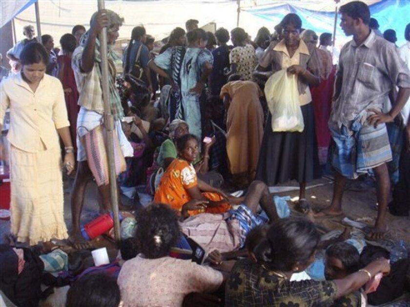 In this photo taken on Saturday, May 9, 2009, Sri Lankan ethnic Tamils take shelter at a makeshift hospital in Mullivaaykaal, Sri Lanka. (AP Photo)