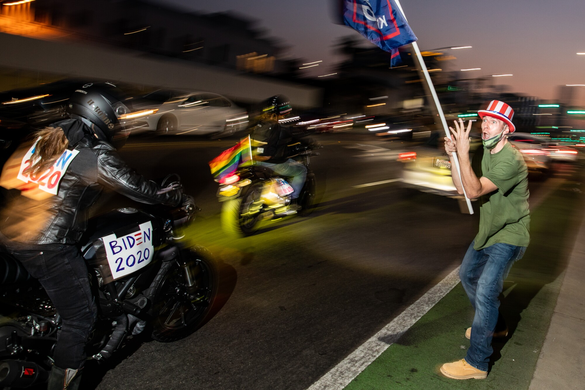 A supporter of President Trump waves a flag as Joe Biden supporters ride by on motorcycles in Beverly Hills