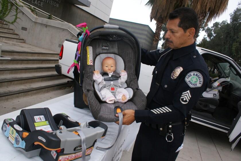 William Bustos, detective de tráfico de LAPD, muestra a que altura debe colocarse el broche del cinturón en los asientos de seguridad de bebés.