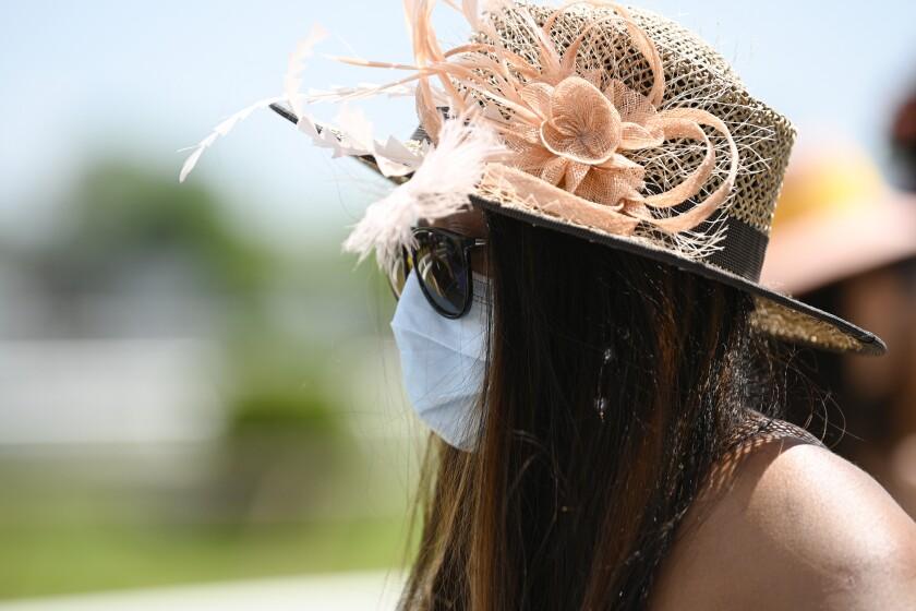 Una mujer usando cubrebocas por el coronavirus llega a una carrera de caballos