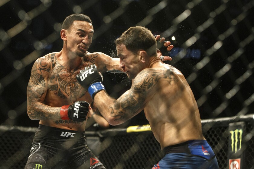 Max Holloway, left, fights Frankie Edgar during a mixed martial arts bout at UFC 240, in Edmonton, Alberta, on Saturday, July 27, 2019. (Jason Franson/The Canadian Press via AP)