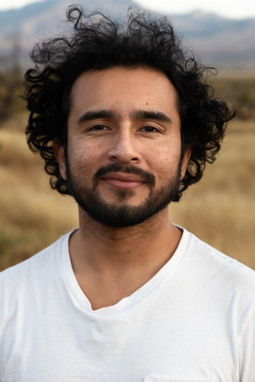 Javier Zamora, a co-founder of Undocupoets, stands near the Douglas, Ariz., port of entry.