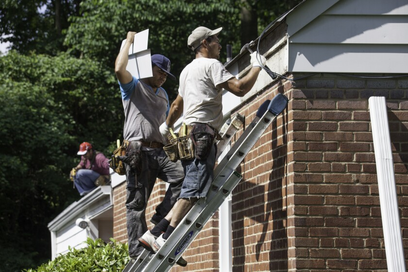 Workers from El Salvador and Honduras replace a home's roof and gutters in Fairfax County, Va., last week. Census Bureau figures show that Latino immigrant population growth in the U.S. has been overtaken by Asians in the last two years.